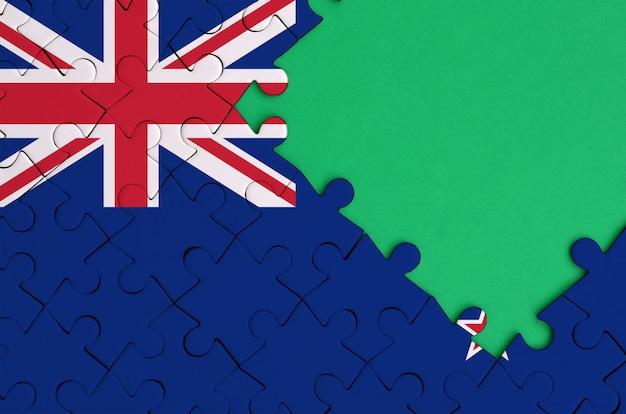 Le Drapeau De La Nouvelle-zélande Est Représenté Sur Un Puzzle Terminé Avec Un Espace De Copie Vert Gratuit Sur Le Côté Droit Photo Premium