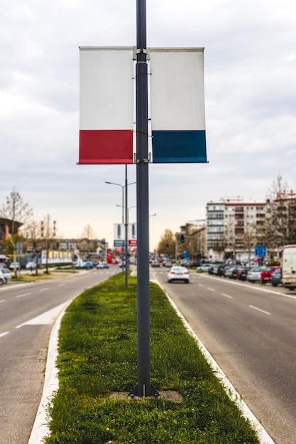 Le drapeau publicitaire blanc double face est accroché au mât du lampadaire Photo gratuit