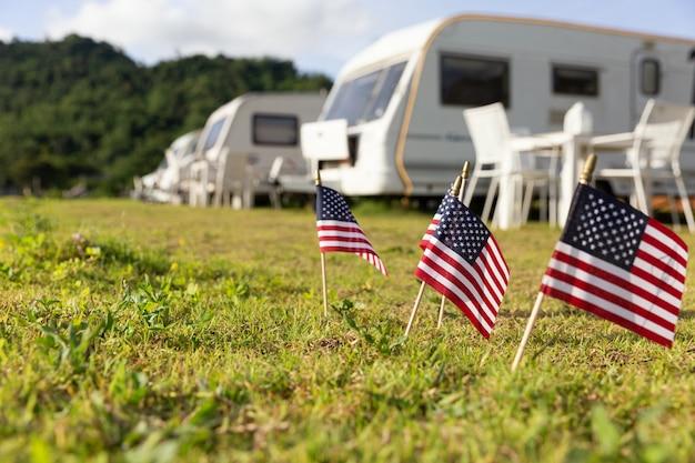 Drapeaux américains et caravanes dans un camping Photo gratuit