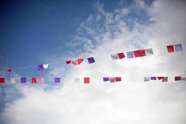 Drapeaux colorés sur un ciel bleu avec des nuages blancs Photo Premium