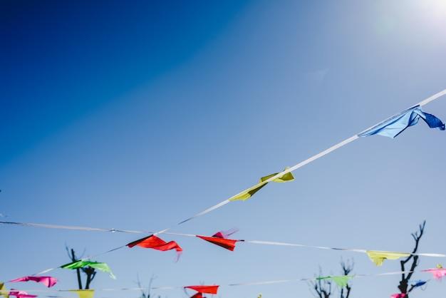 Drapeaux colorés contre le soleil agitant dans le vent lors d'une fête en plein air. Photo Premium