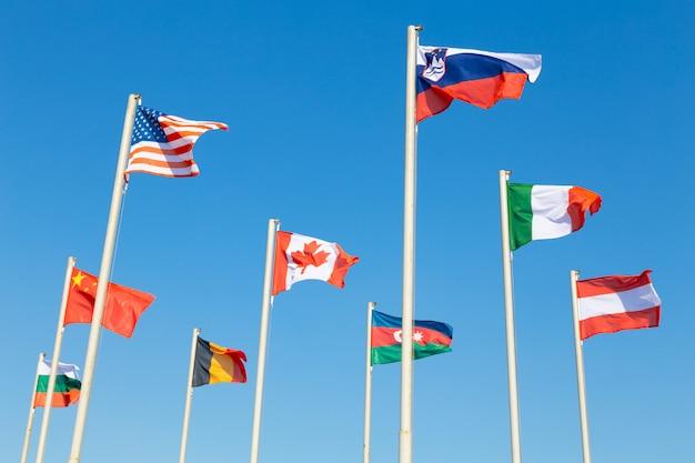 Drapeaux de différents pays flottant contre le ciel bleu Photo Premium