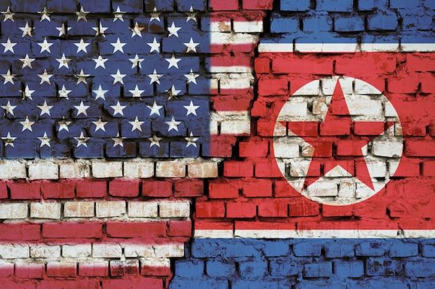 Drapeaux Des états-unis Et De La Corée Du Nord Sur Le Mur De Briques Avec Une Grande Fissure Au Milieu Photo Premium