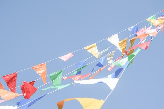 Drapeaux de fête colorés banderoles suspendus sur un ciel bleu pour la décoration de vacances Photo Premium