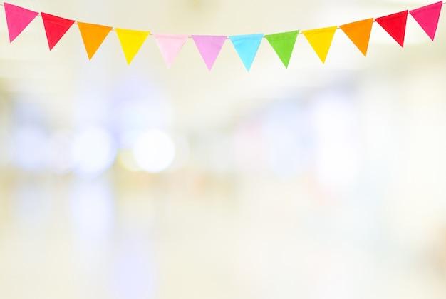 Drapeaux de fête colorés suspendus sur fond abstrait flou Photo Premium