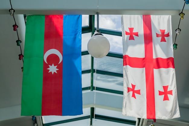Drapeaux de la géorgie et de l'azerbaïdjan suspendus au plafond Photo Premium