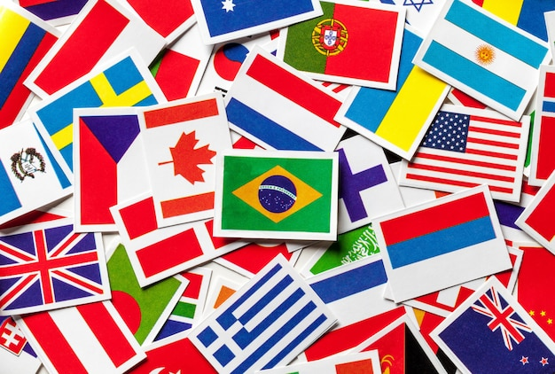 Drapeaux nationaux des différents pays du monde dans un tas dispersé. drapeau brésilien au centre. Photo Premium
