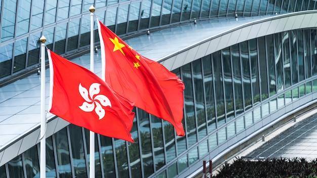 Les drapeaux nationaux de hong kong et de la chine continentale se tiennent ensemble avec l'espace de copie Photo Premium