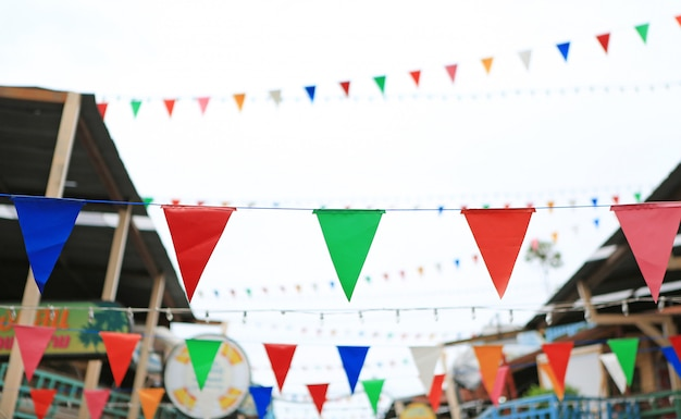 Drapeaux triangulaires multicolores à suspendre entre la vieille maison vintage. Photo Premium