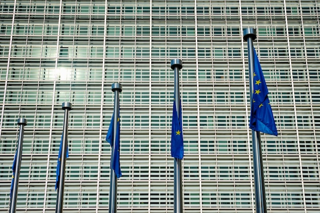 Drapeaux De L'union Européenne Qui Tombent Impuissants Avec Le Bâtiment De La Commission Européenne. Brussles, Belgique Photo Premium