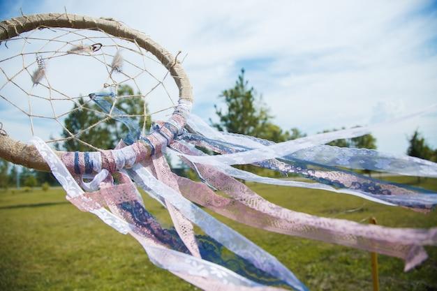 Dreamcatcher bouchent sur un fond d'herbe verte et ciel bleu Photo Premium