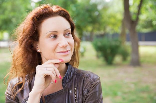 Dreamy jolie demoiselle touchant le menton dans le parc de la ville Photo gratuit