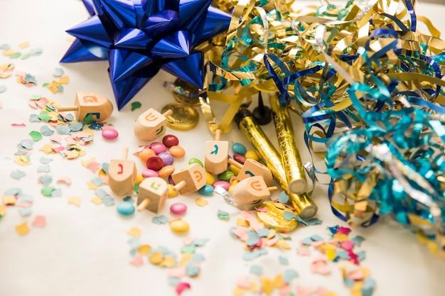 Dreidels et bonbons près de confettis et de guirlandes Photo gratuit