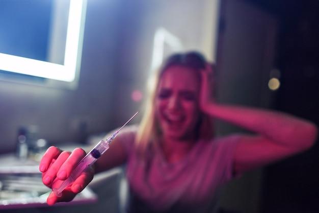 Les Drogues Vous Tuent. Gros Plan De La Seringue à La Main Sur Fond De Femme Toxicomane Hurlant. Non Aux Drogues. 26 Juin, Journée Internationale Contre L'abus Des Drogues. Choisissez La Vie Pas La Drogue Photo Premium