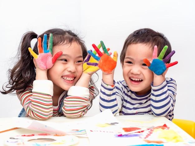 Drôle deux petite fille asiatique jouant des mains de peinture aquarelle. Photo Premium