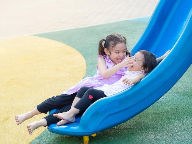 Drôle deux petite fille mignonne jouant glissant sur le terrain de jeu. sœur aînée soigne sa soeur cadette. Photo Premium