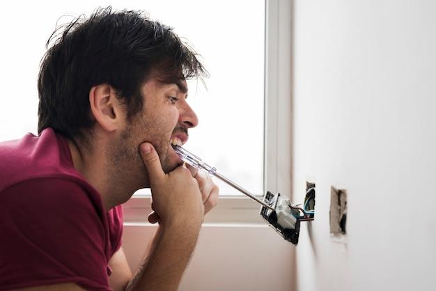 Drôle électricien installant prise avec tournevis portant dans la bouche Photo gratuit