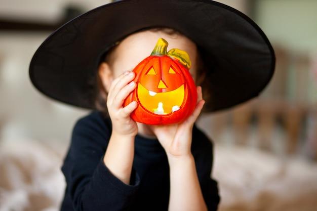 Drôle Enfant Fille En Costume De Sorcière Pour Halloween Avec Citrouille Jack Dans Une Mains Photo Premium