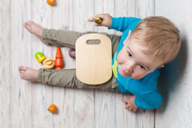 Drôle Enfant Joue Dans Le Chef. Bébé Souriant Coupe Des Légumes En Bois. Intéressant Jeu De Développement Pour Enfants En Sécurité De Près. Photo Premium