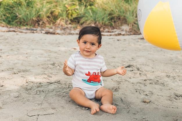 Drôle enfant qui joue sur la plage Photo gratuit
