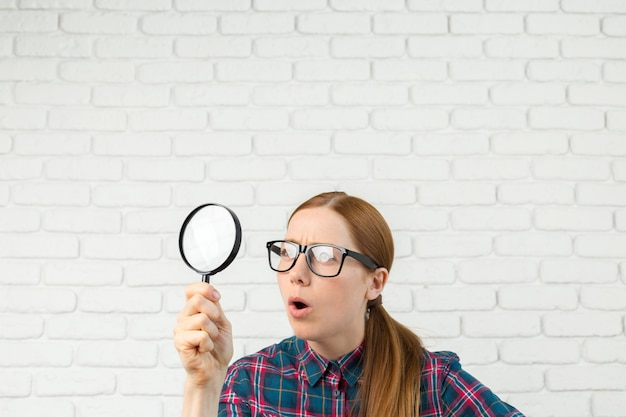 Drôle D'expression, Femme Choquée Regardant à Travers Une Loupe, Photo Premium