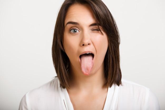 Drôle Femme Clin D'oeil Et Montrer La Langue Photo gratuit