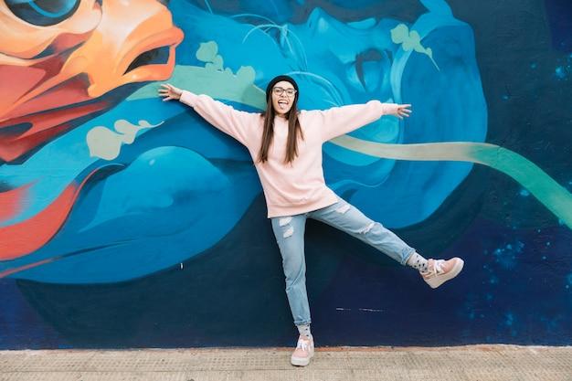 Drôle femme debout devant le mur de graffitis Photo gratuit
