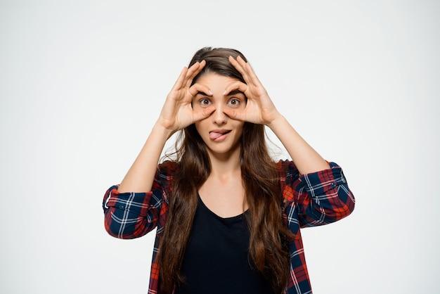 Drôle Femme Faire Des Lunettes Avec Les Mains Et Montrer La Langue Photo gratuit