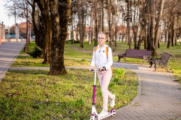 Drôle fille blonde, apprendre à patiner sur un scooter blanc dans le parc vert chaud au centre de la grande ville. activité d'été Photo Premium