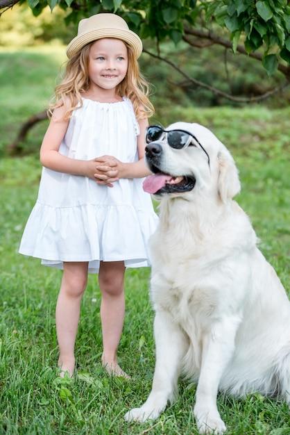 Drôle gros chien à lunettes de soleil et jolie fille blonde en robe blanche à l'extérieur dans le parc. Photo Premium