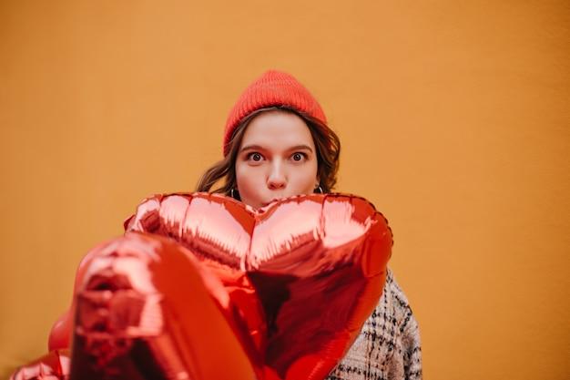 Drôle Jeune Femme Au Chapeau Rouge Couvre Une Partie De Son Visage Avec Un énorme Ballon Brillant Photo gratuit