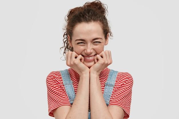 Drôle Jeune Femme Aux Taches De Rousseur Posant Contre Le Mur Blanc Photo gratuit