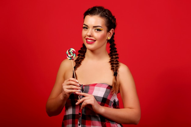 Drôle Jeune Fille Tenant Une Sucette Et Posant Pour Kamerñ ‹sur Mur Rouge, Mur Rouge, Nattes Photo Premium