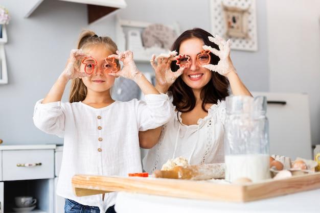 Drôle mère et fille en utilisant des formes de biscuits Photo gratuit