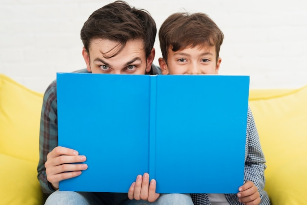Drôle père et fils couvrant leurs visages Photo gratuit