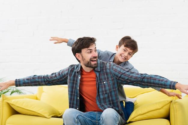 Drôle père et fils jouant sur un canapé Photo gratuit