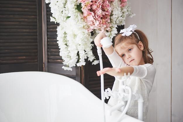 Drôle petite fille aux cheveux bouclés. préparez-vous à prendre un bain. spacieuse salle de bain éclairée. un corps sain et propre. prendre soin de soi depuis son enfance Photo Premium