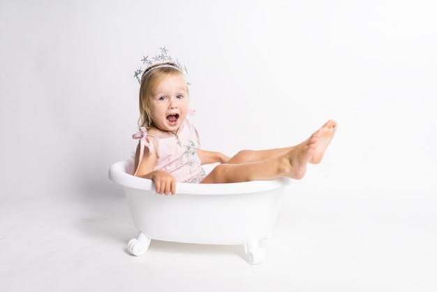 Drôle petite fille blonde s'assoit dans un bain dans le studio Photo gratuit