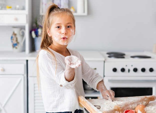 Drôle petite fille montrant sa main avec de la farine Photo gratuit