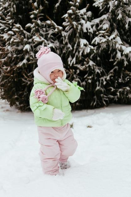 Drôle petite fille s'amuser dans le magnifique parc d'hiver pendant la chute de neige Photo Premium