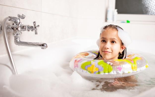 Drôle De Petite Fille Se Baigne Dans Une Baignoire Avec Une Bouée De Sauvetage Gonflable Et Avec De La Mousse Dans L'eau Photo Premium