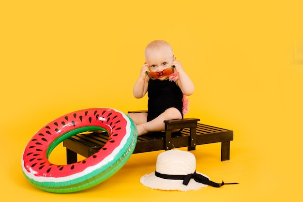 Drôle De Petite Fille Vêtue D'un Maillot De Bain Noir Et Rose, Grand Chapeau Et Lunettes De Soleil Assis Sur Une Chaise Longue En Bois Isolé Sur Jaune Photo Premium