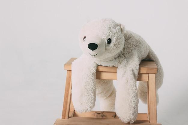 Drôle vieux jouet ours blanc sur une chaise en bois Photo Premium