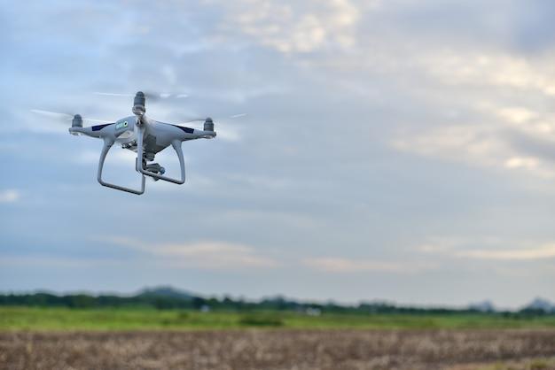 Drone avion décoller de terre au-dessus de champ pour prendre photo aérienne par caméra dans le ciel bleu. Photo Premium