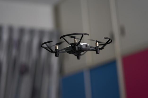 Un drone blanc vole dans les airs à l'intérieur d'un résident en train de jouer avec des turbulences ou des hélices Photo Premium