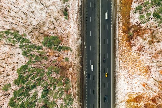 Drone Photo De La Parcelle De Route De Campagne Avec Vue De Dessus De Voitures. Voitures Sur Route Goudronnée Parmi Les Arbres De La Forêt Et Du Paysage En Hiver Photo Premium