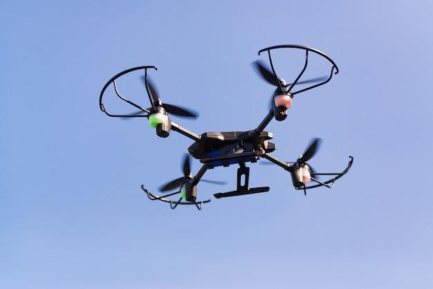 Drone volant ou hélicoptère dans un ciel bleu. Photo Premium
