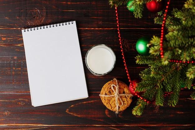 Du lait, des biscuits et une liste de souhaits sous le sapin de noël. le de l'arrivée du père noël. Photo Premium