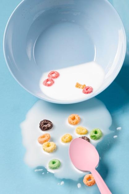 Du lait et des céréales renversés sur toute la table et une cuillère rose Photo gratuit