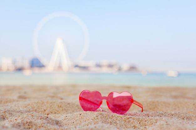 Dubaï, émirats Arabes Unis, Novembre 2019. Lunettes De Soleil Roses Sur Une Plage De Sable Avec Vue Sur L'île Bluewaters Et La Grande Roue Dubai Eye, Lune De Miel, Détente, Espace Copie Photo Premium